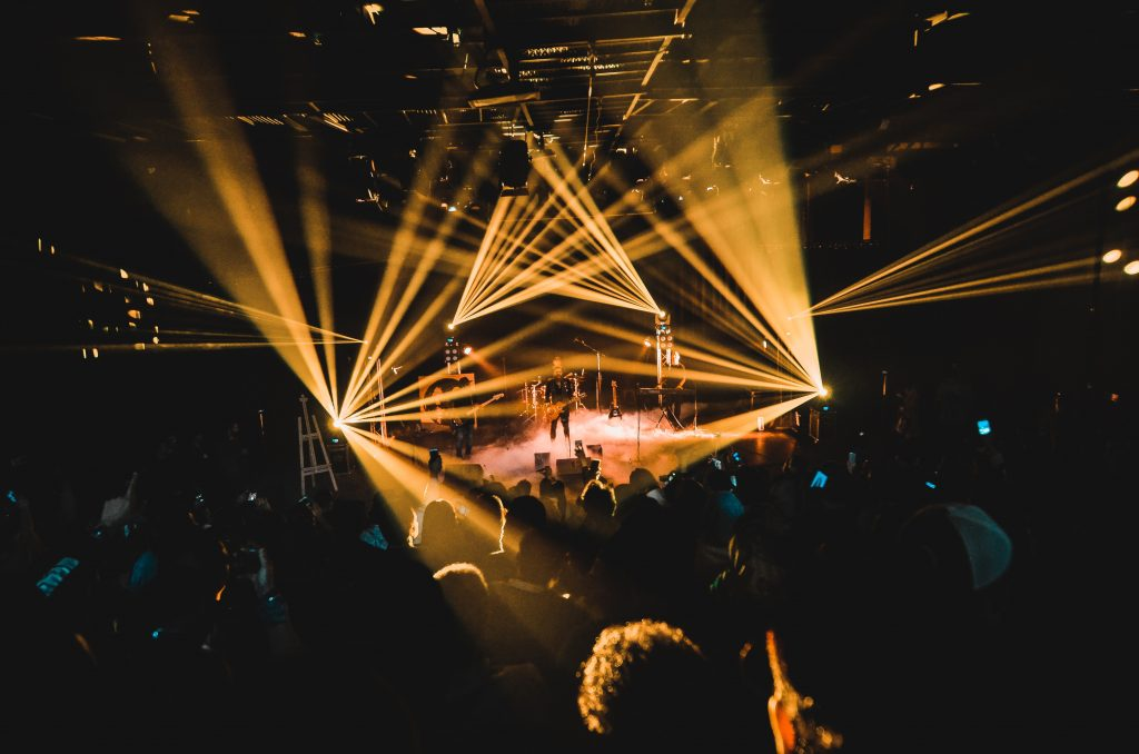 people standing on stage with lights
